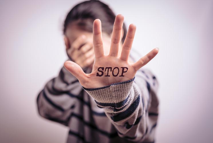 Imagen de mujer con palabra Stop en la palma de la mano