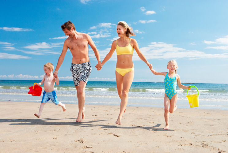 Imagen de familia corriendo por la playa