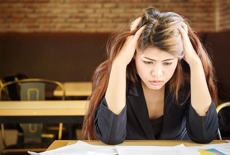 Mujer con manos en la cabeza y actitud de preocupación