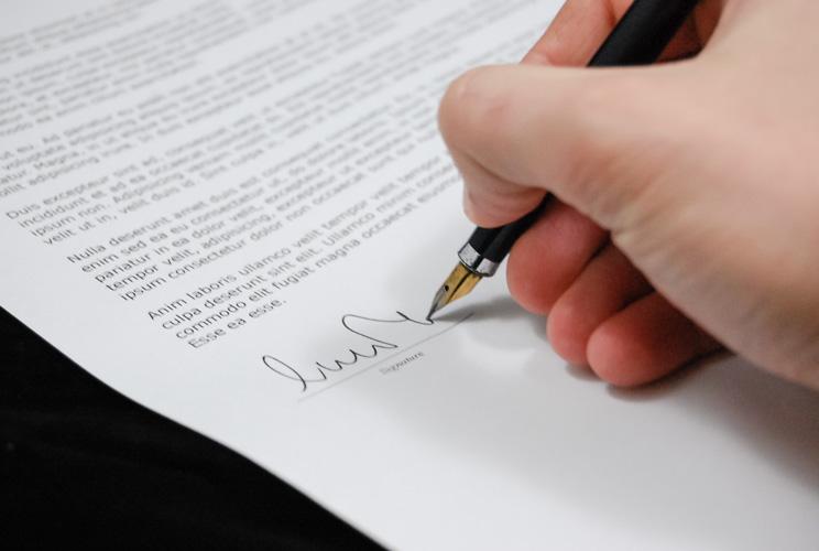 Imagen de mano con pluma firmando en una hoja