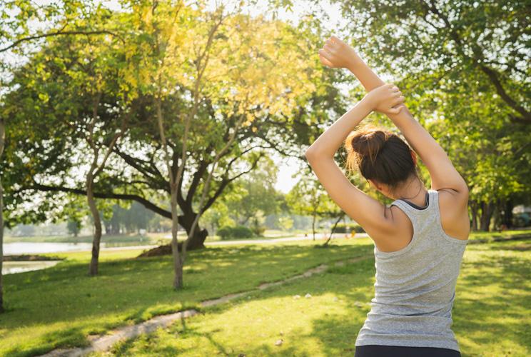 Imagen de mujer haciendo estiramientos en un parque