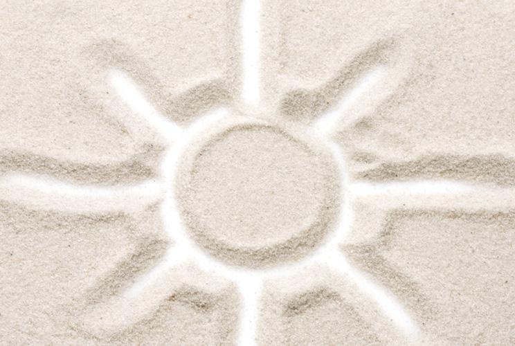 Imagen de un sol dibujado en la arena
