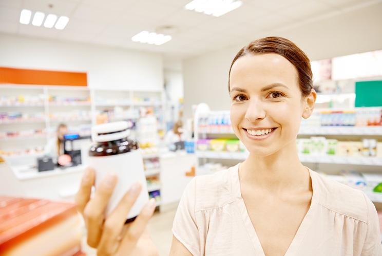 Imagen de una mujer en una farmacia con un bote en la mano