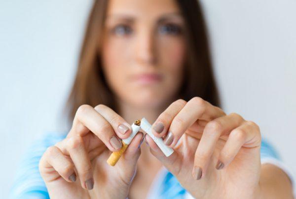 Imagen de una mujer rompiendo un cigarrillo